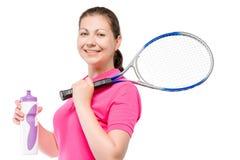 有球拍和一个瓶的30岁的网球员水 免版税库存图片