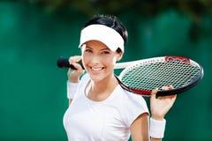 有球拍的俏丽的女运动员在网球场 库存图片