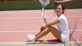 有球拍的微笑的妇女坐网球场 影视素材