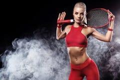 有球拍的美丽的白肤金发的体育女子网球员在红色服装 免版税库存图片