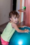 有球有氧运动的女婴在屋子里 免版税库存照片