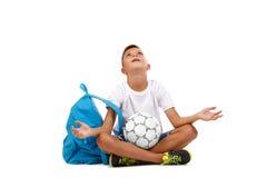有球的一个小男孩在瑜伽姿势被隔绝坐白色背景 足球运动员为胜利祈祷 免版税库存照片