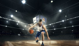 有球的一个蓝球运动员在体育场 basketboll自由式作用 库存照片