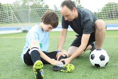 有球的一位年轻足球运动员在领域 免版税库存照片