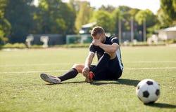 有球的受伤的足球运动员在橄榄球场 免版税库存图片