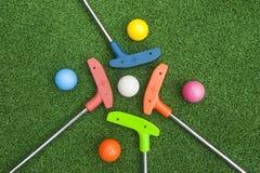 有球的四根微型高尔夫球轻击棒 免版税库存照片