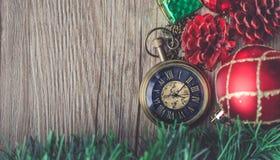 有球的圣诞节怀表和在木后面的礼物盒 免版税库存图片