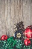 有球的圣诞节怀表和在木后面的礼物盒 免版税库存照片
