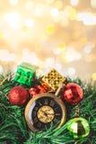 有球的圣诞节怀表和礼物盒在迷离背景中 图库摄影