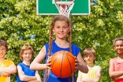 有球的女孩和站立她的队后边 免版税库存照片