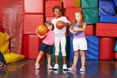 有球的女孩在幼儿园健身房  免版税库存图片
