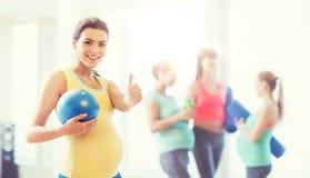 有球的孕妇在显示赞许的健身房 免版税库存照片