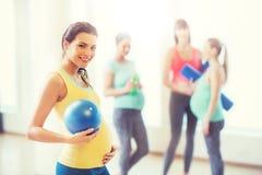 有球的愉快的孕妇在健身房 免版税库存图片