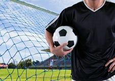 有球的足球运动员在他的在目标前面的胳膊 库存图片