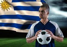 有球的足球运动员在他的在领域的手上 风暴 后边旗子 库存图片
