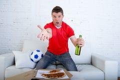 有球的年轻支持者人和在家坐长沙发的电视上的啤酒瓶观看的橄榄球赛 免版税图库摄影