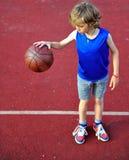 有球的年轻蓝球运动员 免版税库存图片