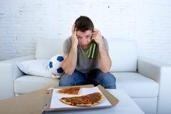 有球薄饼和啤酒瓶观看的橄榄球赛的人在电视覆盖物注视哀伤和失望失败或失败的 免版税库存照片