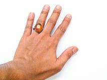 有琥珀色的圆环的一只人手在白色后面隔绝的他的手指 库存图片