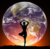 有瑜伽姿势的妇女在地球的背景 库存图片