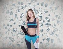 有瑜伽席子的在混凝土墙上的女孩和剪影 免版税库存照片