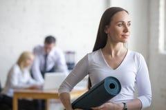 有瑜伽席子的女商人 免版税库存照片