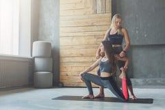 有瑜伽辅导员的少妇健身俱乐部的,美人鱼姿势 免版税库存图片
