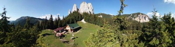 有瑞士山中的牧人小屋的美好的山土坎全景 库存图片