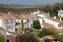 有瓦屋顶的农村白色房子沿古老墙壁 免版税库存照片