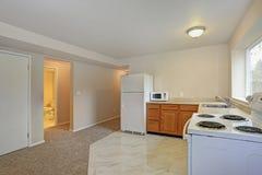 有瓦片地板的新近地被更新的L形的厨房 免版税库存照片