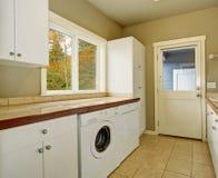 有瓦片柜台和水槽的洗衣房 图库摄影