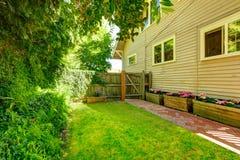 有瓦片砖走道和木门的后院 免版税库存照片