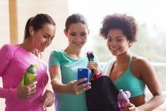 有瓶和智能手机的愉快的妇女在健身房 免版税库存图片