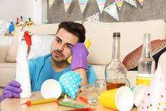 有瓶洗涤剂和旧布的疲乏的年轻人在杂乱屋子里 免版税库存照片