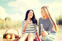 有瓶的女朋友在海滩的啤酒 免版税库存照片