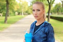 有瓶的妇女蛋白质震动在公园 图库摄影