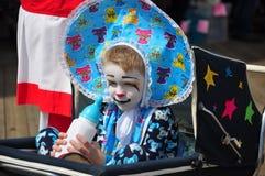 有瓶的小小丑在婴儿推车 免版税图库摄影