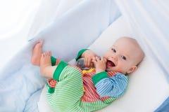 有瓶的小婴孩在白色床上 库存图片