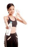 有瓶的美丽的亚裔健康女孩饮用水 免版税库存图片