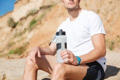 有瓶的运动员水坐海滩 图库摄影
