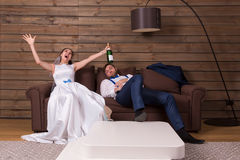 有瓶的醉酒的新娘,睡觉在长沙发的新郎 免版税库存图片