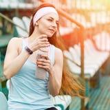 有瓶的年轻微笑的女运动员水 库存照片