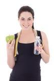 有瓶的年轻美丽的运动的妇女水、苹果和mea 免版税库存照片