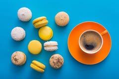 有甜五颜六色的macarons的咖啡杯 免版税库存照片
