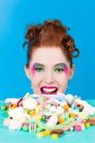 有甜好吃的东西和糖果的女孩 免版税库存照片