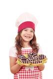 有甜巧克力油炸圈饼的小女孩厨师 免版税库存照片