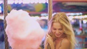 有甜棉绒的可爱的年轻白肤金发的女孩在转盘乘坐并且微笑 跳舞和无所事事  慢 影视素材