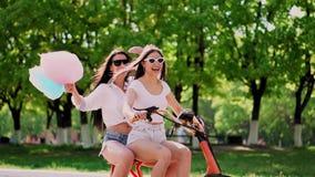 有甜棉花的性感的女孩在短的短裤在公园乘坐一辆电滑行车 股票视频