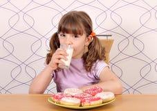 有甜油炸圈饼和牛奶的小女孩 免版税库存照片