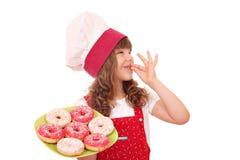 有甜油炸圈饼的小女孩厨师 图库摄影